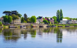 Breathtaking view on amazing small town Saumur, France. Many gray houses near Loire river, lots of green trees, a row of colorful boats. Warm spring morning, vibrant blue sky, calm atmosphere