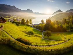 Breathtaking views of the morning green garden in sunlight. Location place resort Grundlsee, Liezen District of Styria, Austria, Alps. Europe. Vibrant photo wallpaper. Discover the beauty of earth.
