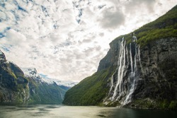 Breathtaking wide view of Geirangerfjord and seven sisters waterfall during golden hour. The most famous fjord in Norway