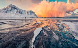Breathtaking winter view of Lofoten Islands, Norway, Europe. Storm clouds illuminated of the first rays of sunrise. Great morning view of popular tourist destination - Skagsanden beach.