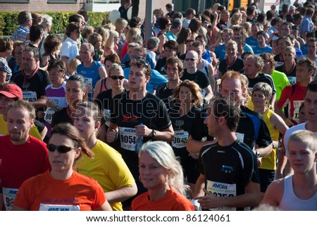 BREDA, NETHERLANDS – OCT. 2: Singelloop (Canal Run), Closeup of runners shortly after the start of the 10 km run of the Singelloop in the Dutch city of Breda in the Netherlands on October 2, 2011. - stock photo