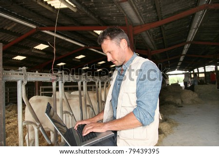 Breeder in barn with laptop computer