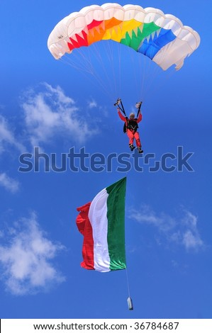 BRESCIA, ITALY - SEPTEMBER 6: sport parachutist in mid-air with large italian flag during Brixia Air Show.  on September 6, 2009 in Brescia