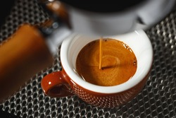Brew espresso from a coffee machine into a brown porcelain cup