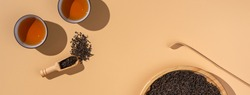 Brewed black puer tea in ceramic bowls,dry pu-erh tea leaves in a wooden bamboo plate on a beige background,tea ceremony