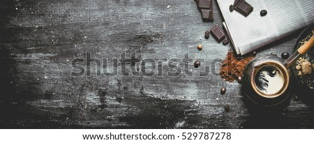 Brewed coffee pot with fresh newspaper and bitter chocolate. On black rustic background. #529787278