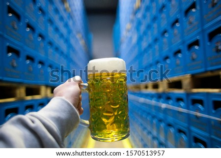 Brewer holding one liter glass of beer in warehouse with beer crates