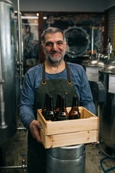 brewer holding wooden crate with glass beer bottles in his craft beer brewery