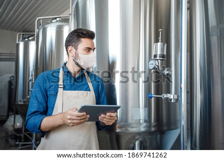Brewery, startup, small business and covid-19 quarantine. Young handsome man owner in apron and protective mask holds tablet and looks at equipment for fermentation in plant, free space Foto stock ©