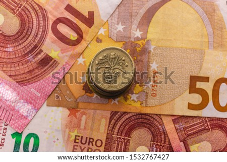 Brexit. Confrontation between Europe and England. Political concept. A stack of one pound sterling coins on a background of Euro banknotes. #1532767427