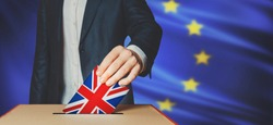Brexit Voting concept. Unrecognizable man voter holds in his hand ballot box Greatbritain flag