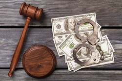 Bribe and corruption concept. Top view us dollars money with handcuffs and wooden gavel.