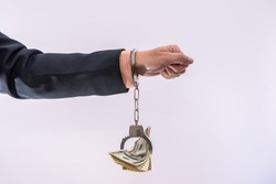 Bribe or corruption concept male hands hold dollar bills in handcuff. criminal