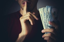 Bribery people with dollar bills in hand and quiet gesture