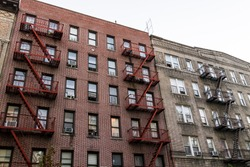 Brick apartment condo building exterior architecture in Fordham Heights center, Bronx, NYC, Manhattan, New York City with fire escapes, windows, ac units in evening