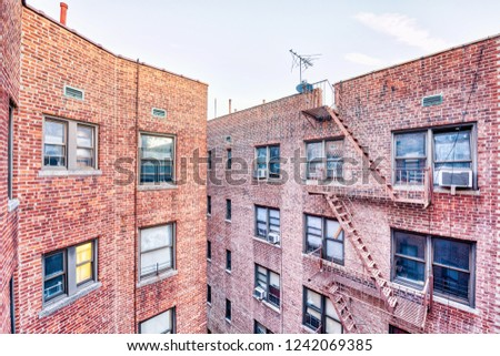 Brick apartment condo building roof exterior architecture in Fordham Heights center, Bronx, NYC, Manhattan, New York City with fire escapes, windows, ac units in morning, satellite dish, antenna, USA