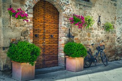 Brick arch entrance with wooden door. Entrance decorated with flowerpots and colorful flowers. Street view with entrance and parked bicycle, Pienza, Tuscany, Italy, Europe