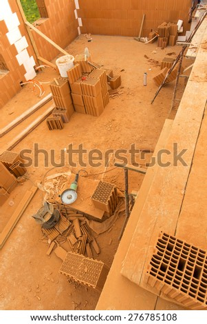 Brick by Brick,  build a house on your own. Building a home. Power tools on the dusty construction site. House under construction.