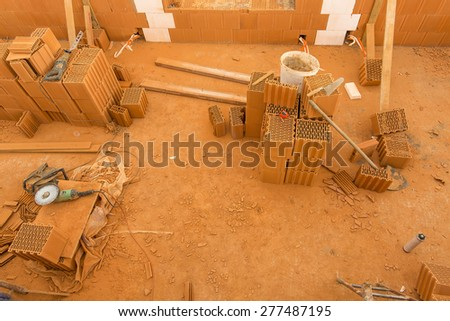 Brick by Brick,  build a house on your own. Building a home. Power tools on the dusty construction site. House under construction