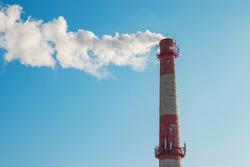 Brick chimney with white smoke on a blue sky background