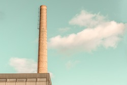 Brick Factory or Industrial Chimney with Steel Confining Rings against Teal Sky with Fluffy Clouds. Minimal Aesthetics. High Resolution Photography.