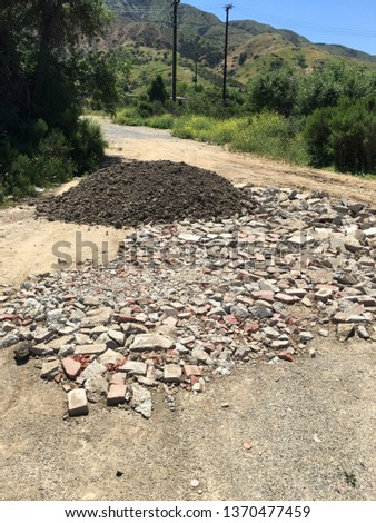 Brick fragments and a pile of dirt on a dirt road off the interstate in Corona, CA. #1370477459