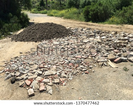 Brick fragments and a pile of dirt on a dirt road off the interstate in Corona, CA. #1370477462