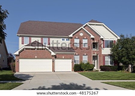 Brick home in suburbs with three car garage