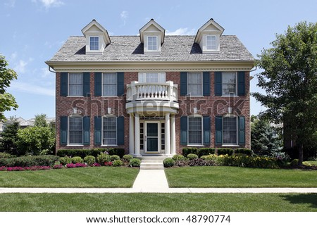 Brick home with front balcony and blue shutters
