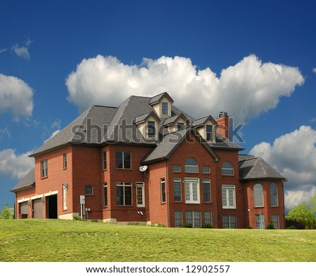 Brick Mansion - a 4 story brick mansion with a three car garage, sitting on a hillside.