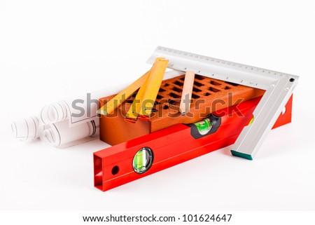 brick, mason tools and construction plans isolated on white background