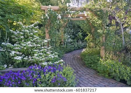Brick pathway through a country garden