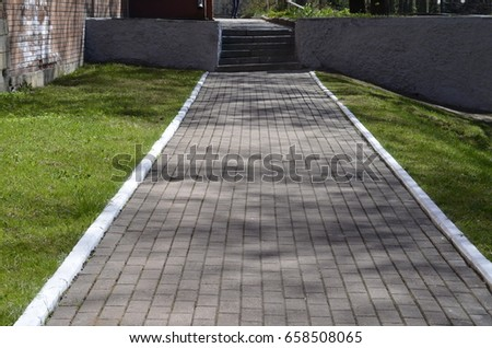 Brick pave sidewalks with grass on the both side #658508065