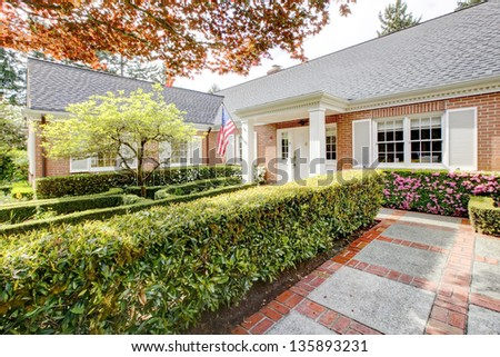 Brick red house with English garden and white window shutters. Summer landscape.