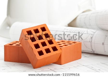 Brick stones on home construction blueprints - house building or construction concept - stock photo