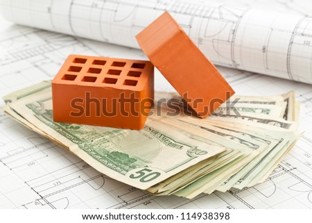 Brick stones with dollar banknotes on home construction blueprints - home or construction financing concept