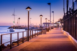 Brick walkway to boat dock in early morning sunrise light, streelights on, shadows, quiet, calm peaceful, Avalon, Santa Catalina Island, California