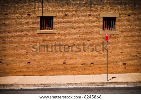 Brick wall and No Stopping sign in back street - ideal grunge background