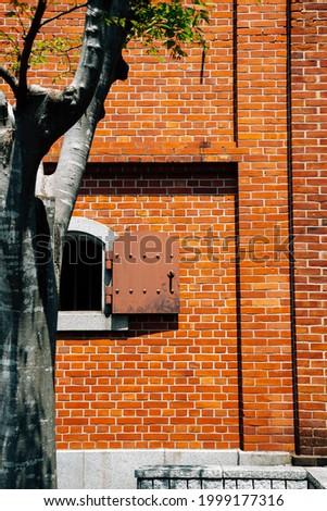 Brick wall and tree, Ozu Redbrick Hall Akarenga-kan in Ehime, Shikoku, Japan Stockfoto ©