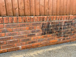 Brick wall being cleaned. Dirt and grime can be seen on the part which has not been pressure washed
