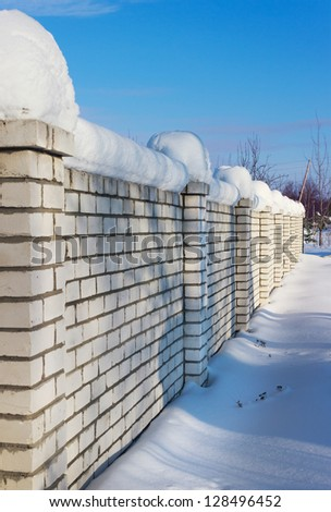 Brick wall, covered with snow in January in rural areas