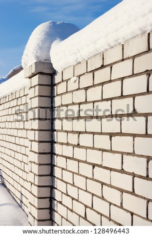 Brick wall, covered with snow  in rural areas