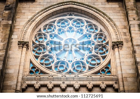 Brick wall has big glass window with arch in traditional gothic style. Round stone details with ornate pattern. Classic spanish design of old building. Famous tourist place in Spain, Europe.