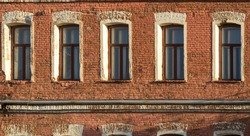 Brick wall of an old 19th century building with large windows. Five large windows in an old red brick building.