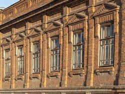 Brick wall of an old 19th century building with large windows. Six large windows in an old red brick building.