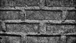 Brick wall pattern and texture in black and white with high contrast and noise/grainy also with HDR processes. Suitable for wallpaper or background