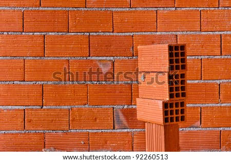 Brick wall with a stack of new bricks