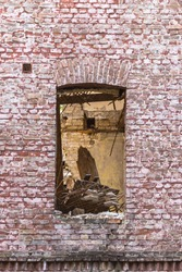 Brick wall with a window. Old house. Destroyed building. Empty window opening. cityscape. Old and new building. City building. Masonry. Ruins on the site of a residential building.