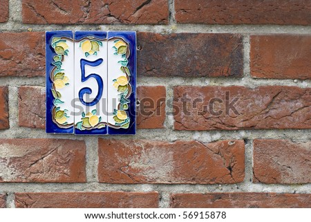 Brick wall with house number plate. Suffolk, England