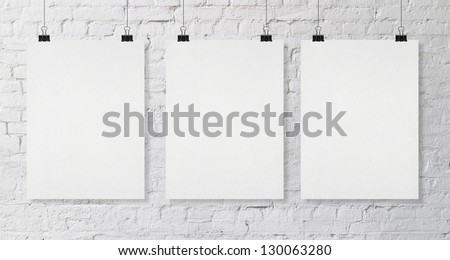 brick wall with three blank poster